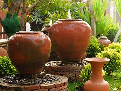 Average fountain with 3 large clay pots ensemble, bricks base, and lots of green plants around.