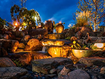 Large, complex ensemble of stone rocks fountain, with waterfalls on different levels, lighting at night, and plants all around it.