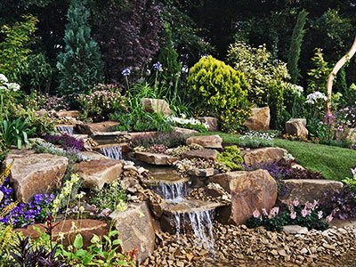 Large pondless water feature, with complex waterfall, stone steps, and lush greenery around.