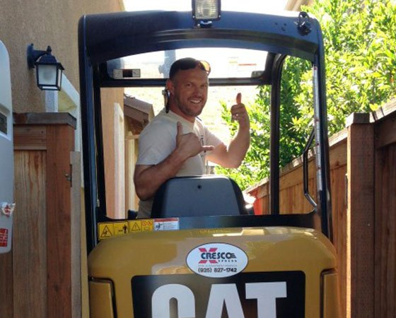 Owner driving a CAT machine on construction site.