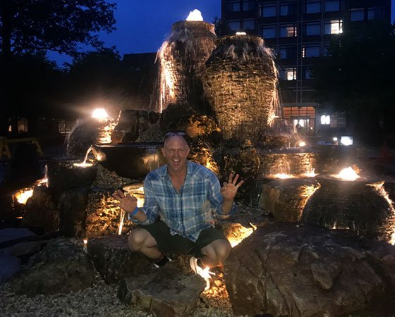 Owner waving in front of recently finished water feature, in the evening.