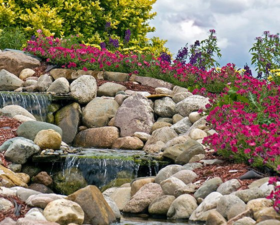Pondless water feature with two small, stone steps, small waterfall, stone rocks, and colorful plants.