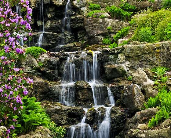 Pondless water feature with high waterfall falling on stone stairs, surrounded by lush greenery and flowers.