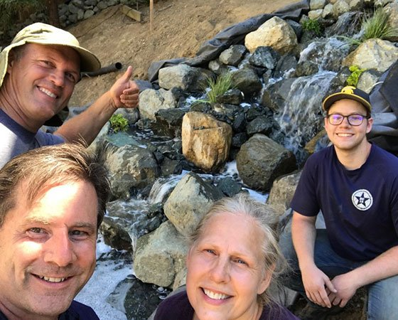 Team at work, building a pondless water feature with a waterfall.